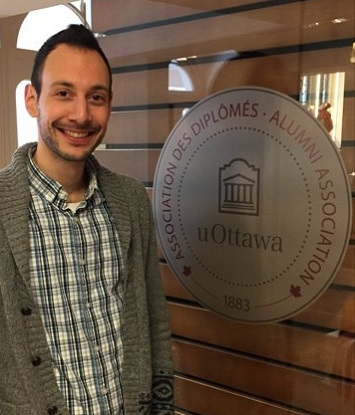 Un homme se tient debout près d'un logo de l'Association des diplômés de l'Université d'Ottawa.