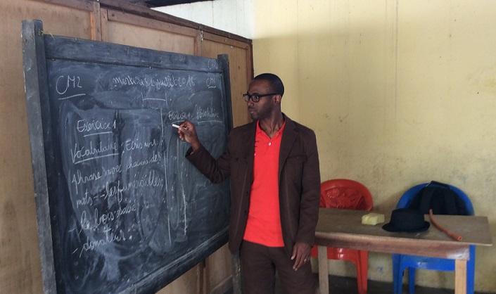 Ouatina Bamba écrit sur un tableau dans une salle de classe en Côte d'Ivoire.