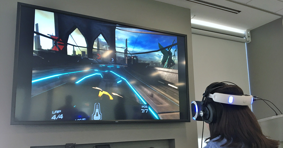 A student, wearing a headset, plays a video game on a TV screen.