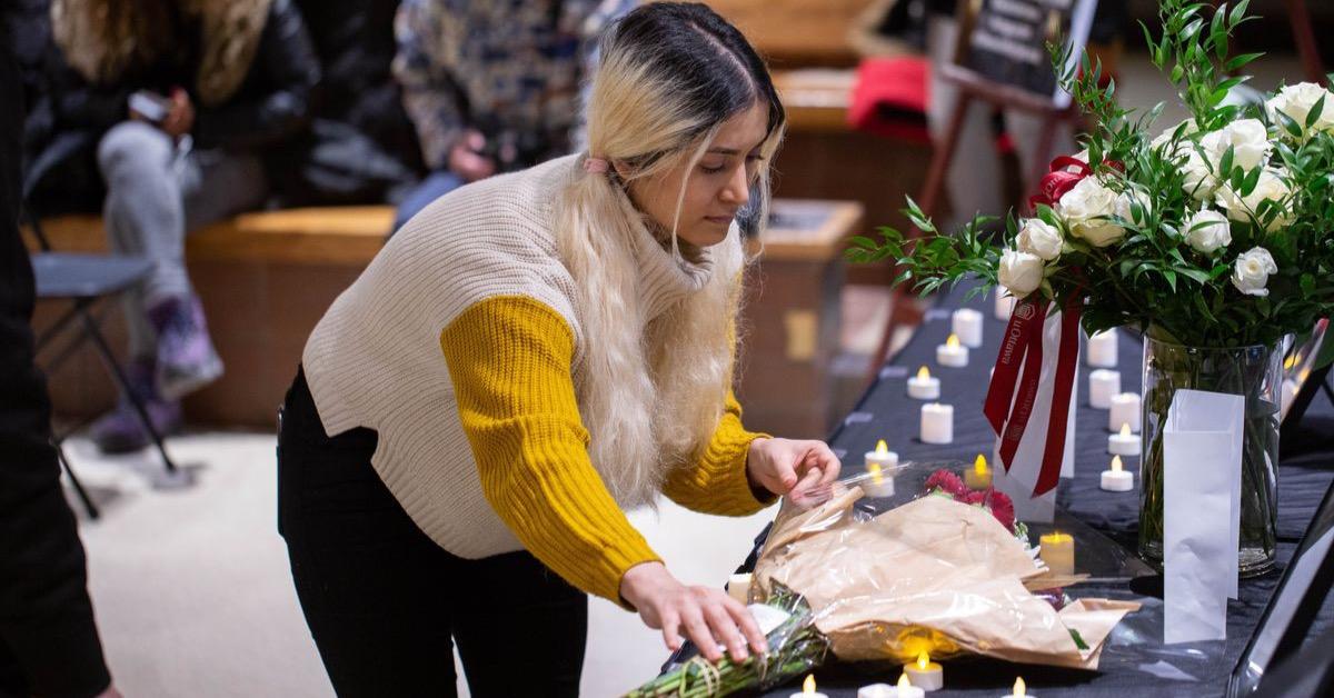 Une jeune femme dépose une gerbe de fleurs sur une table de commémoration