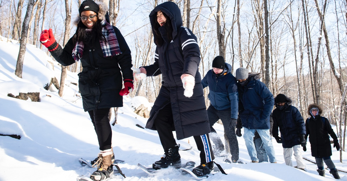 A group of students snowshoeing in a winter setting in the woods