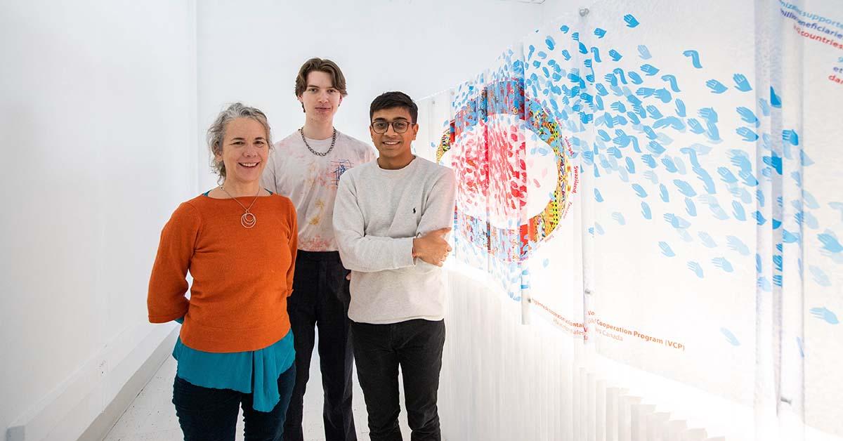 Jennifer Macklem, Willem Deisinger, and Devansh Shah standing beside their art installation