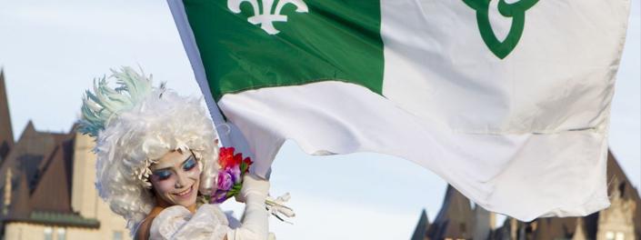 Jeune femme costumée tenant le drapeau franco-ontarien.