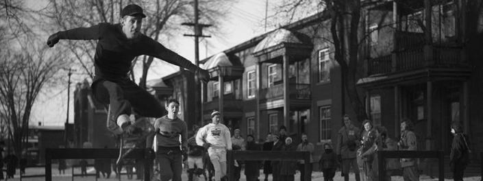 Jeune homme en raquettes sautant par dessus un obstacle sur l'avenue King Edward enneigée.