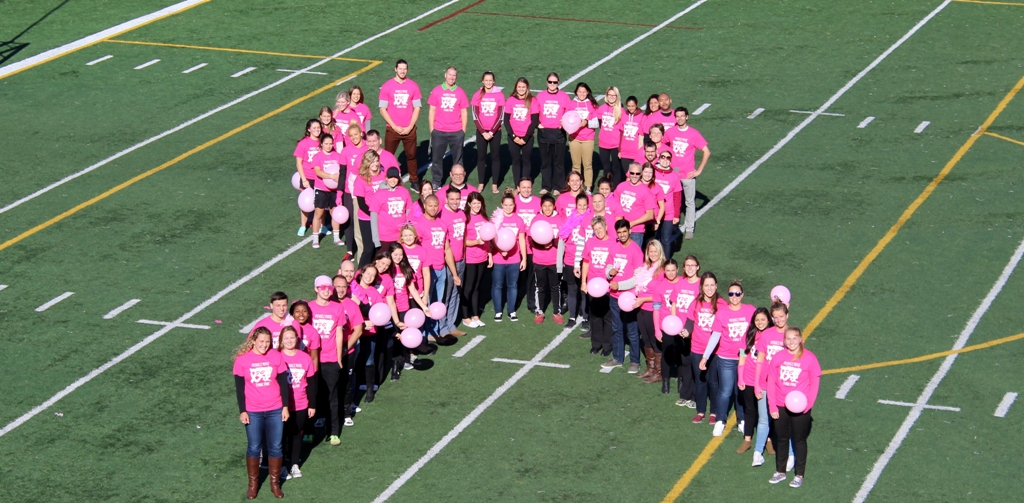 A group of athletes are in a ribbon formation on a football field. They are all wearing pink t-shirts.