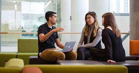 Trois étudiants sont assis et discutent entre eux