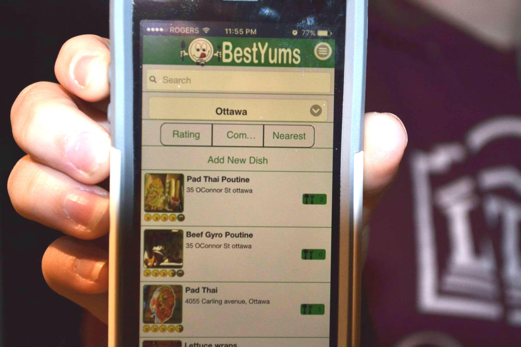 Une personne tenant un appareil mobile sur l'écran duquel on voit l'application.