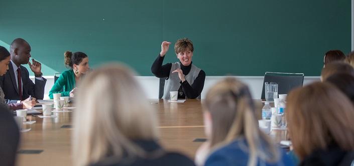 Une femme sourit et fait des gestes en s'adressant à des étudiants réunis autour d'une table.