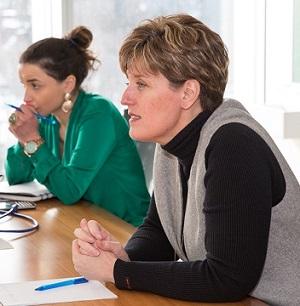 Deux femmes accoudées à une table prêtent l'oreille.