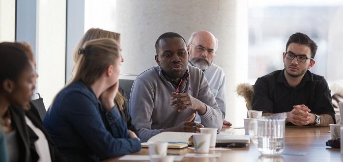Un étudiant prend la parole, tandis que d'autres lui prêtent leur attention.