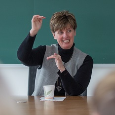 A woman smiles and gestures with her hands as she speaks to students