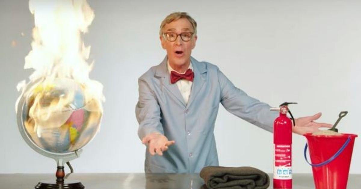Bill Nye The Science Guy s'exprime derrière une table. Un globe terrestre en feu, une couverture, un extincteur et un seau contenant du sable et une pelle sont sur la table.