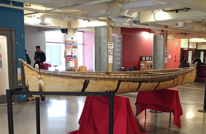 A canoe on exhibition in a room.