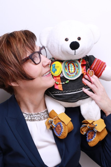 Cindy Blackstock holds close a smiling teddy bear in beaded moccasins.