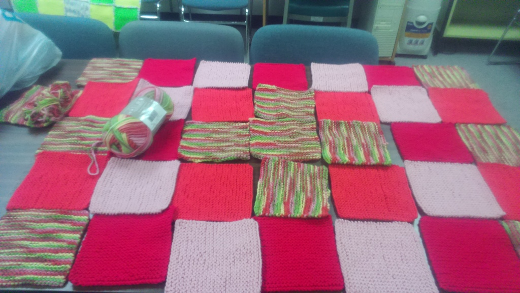 Colourful squares of knitting assembled on a table