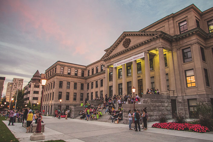 Students on the steps at the front of Tabaret Hall, at dusk.