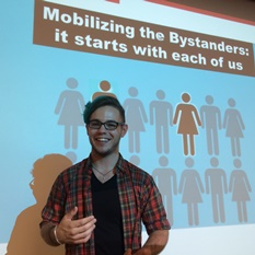 "Man in front of a projected image with the words ""Mobilizing the Bystanders: it starts with all of us"" in the background, and icons of women and men."