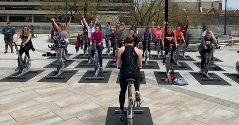 A group of people in the University Square take part in a spinning class.
