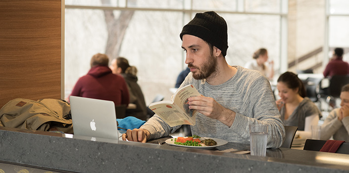 A man wearing a beanie and holding a book uses his laptop while eating.