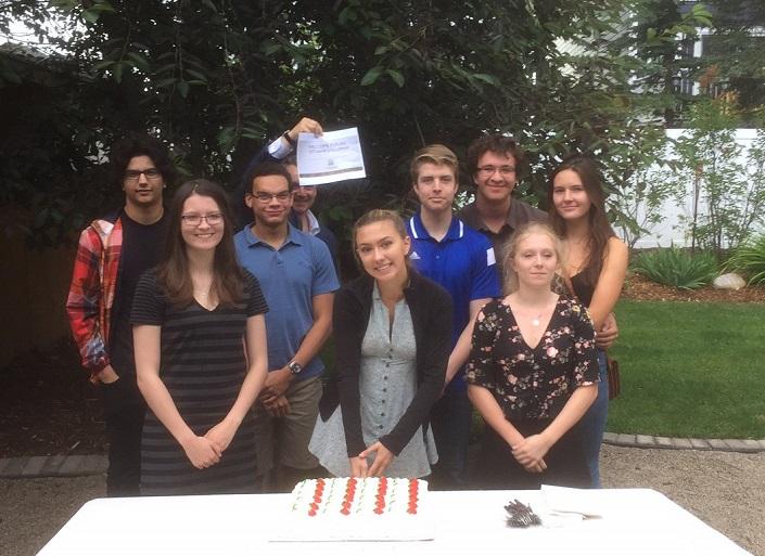 Un groupe de jeunes sont debout derrière une table avec un gâteau.