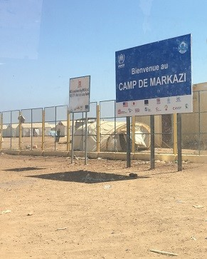 Un panneau en français est érigé à l'extérieur du camp de réfugiés – on y lit « Bienvenue au camp de Markazi ».