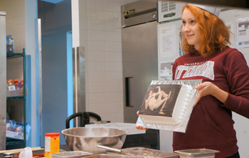 Katy Raymond holds up a cake with a picture of Morgan Briault looking distressed.