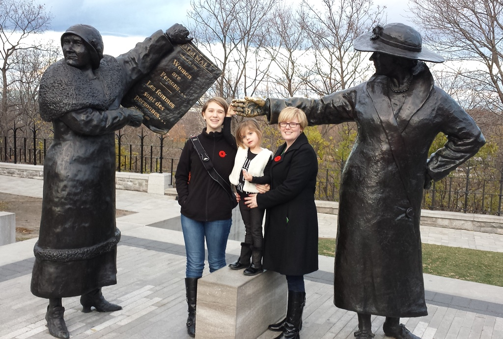 Carla Qualtrough poses by two statues of women with her two daughters