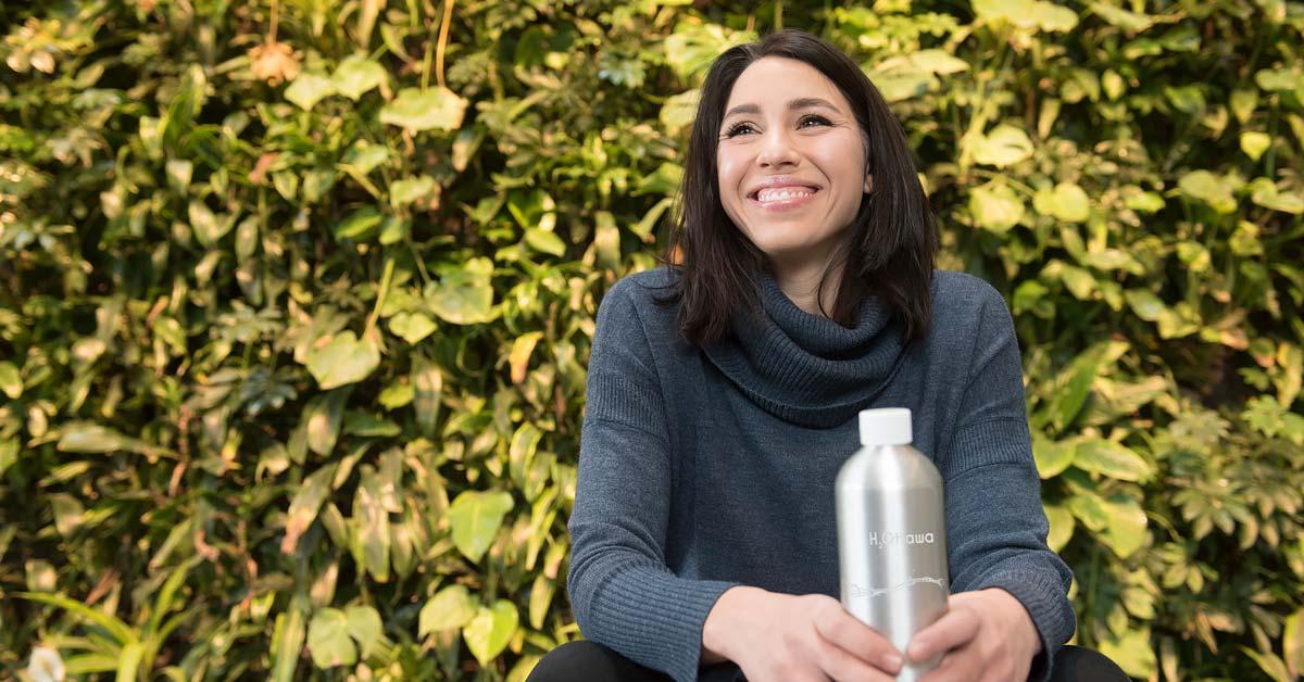 Celeste tient sa bouteille H2Ottawa devant un mur de feuillage