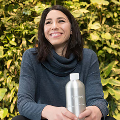 Student Celeste Digiovanni holding her H2Ottawa bottle in front of the live foliage wall of FSS building at uOttawa