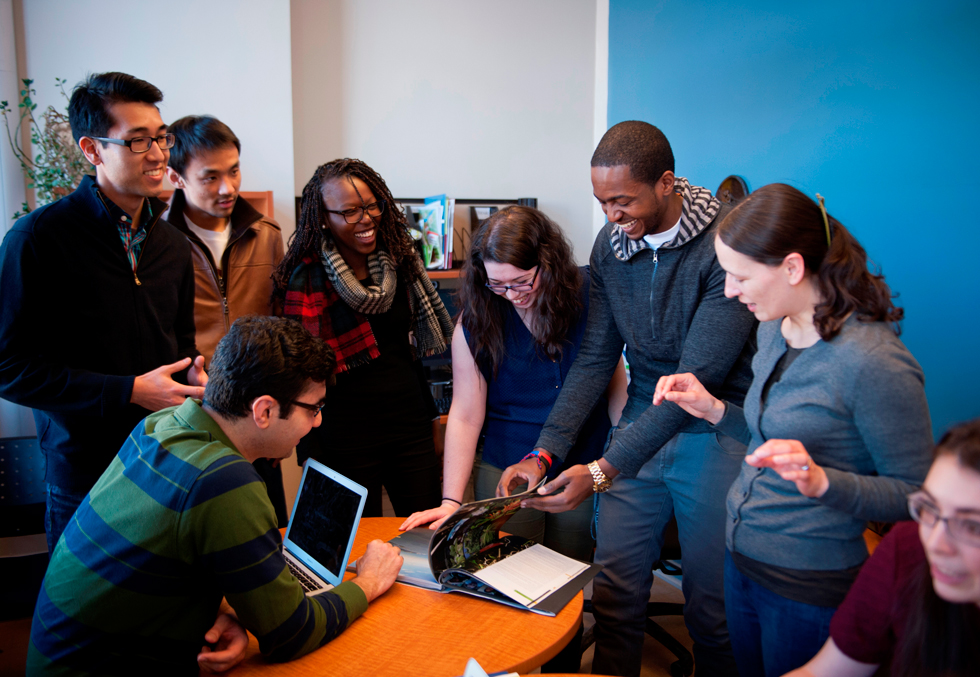 Group of smiling students standing or sitting around a table. They watch as one of the men flips through a magazine.