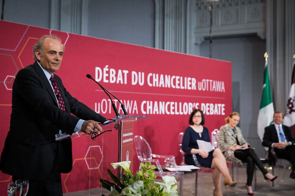 uOttawa chancellor Calin Rovinescu stands at a podium. Other debaters sit in the background.