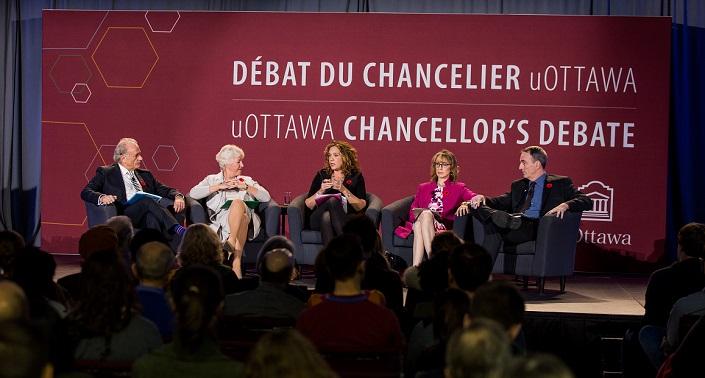 Trois femmes et deux hommes assis dans des fauteuils sur une scène. Le logo des Débats du chancelier est en toile de fond