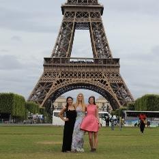Trois femmes, dont Chelsea Cooligan, devant la tour Eiffel.