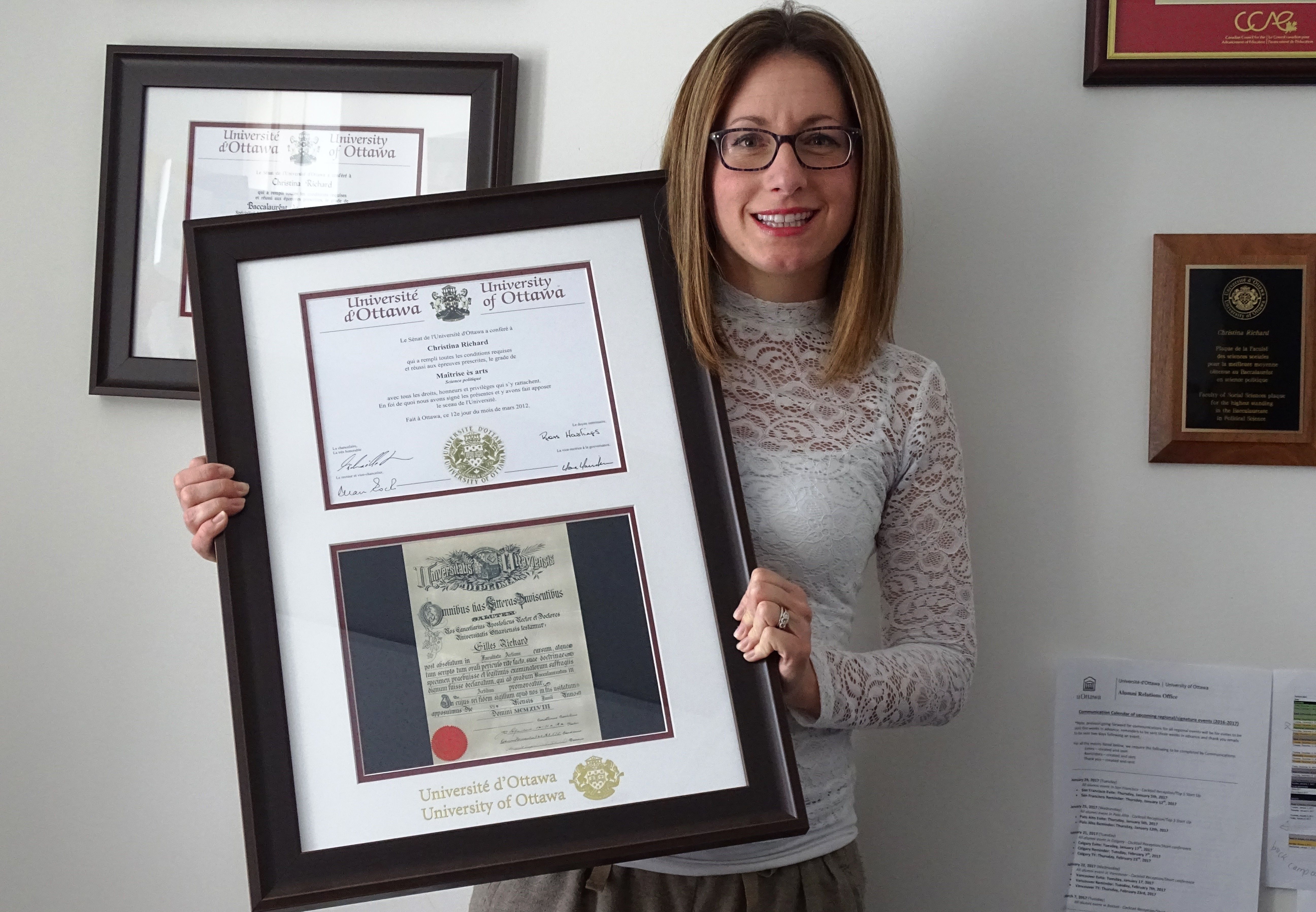 Christina Richard holds her paternal grandfather's framed diploma.