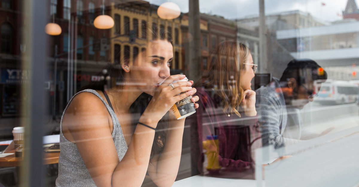 Student in a coffee shop dreamily looking out the window.