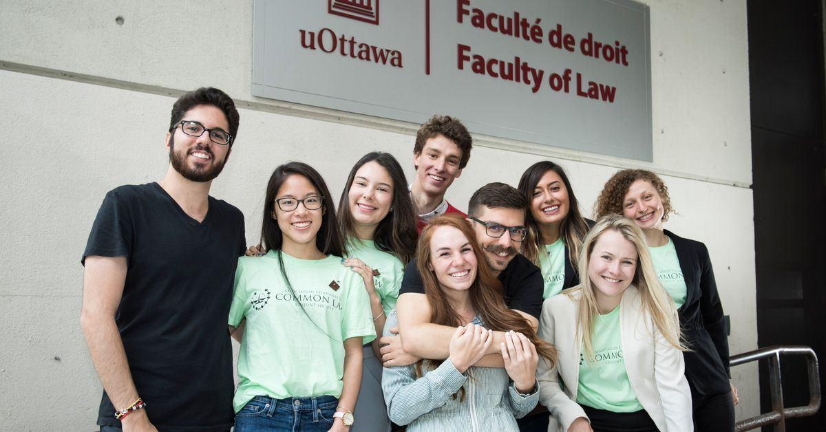 Des étudiants en droit posent debout devant l'enseigne de la Faculté de droit.