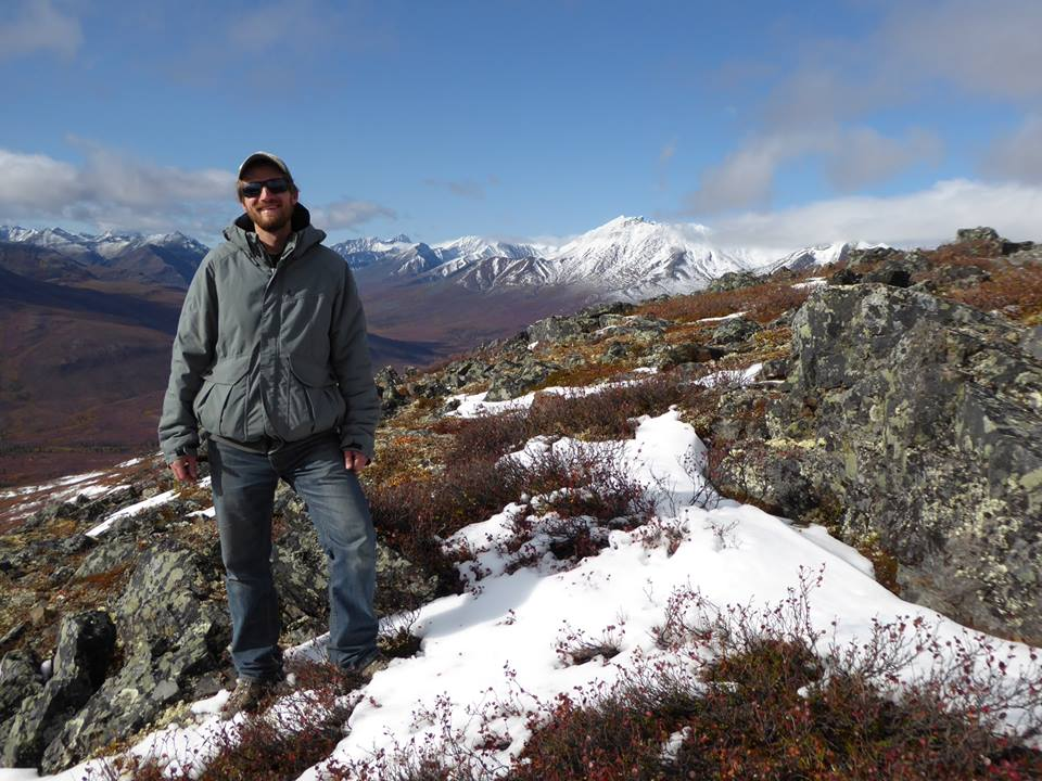 Jesse Cooke stands in front of a mountainous skyline in Tombstone Park, Yukon.