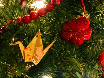 A paper crane, a string of cranberries and a knitted flower decorate a Christmas tree.