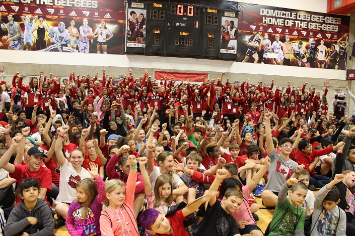 Large group of children at the forefront and adults in red tracksuits in the background, all raising their arms up in a gymnasium