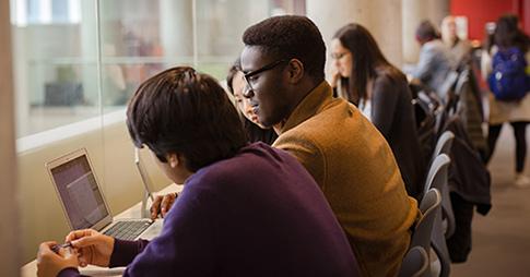 Trois étudiants regardent un ordinateur portable.