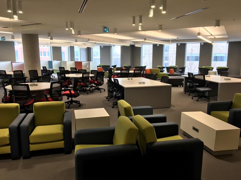 Espace de travail à aire ouverte où se trouvent des bureaux ainsi que des tables de travail et des fauteuils.
