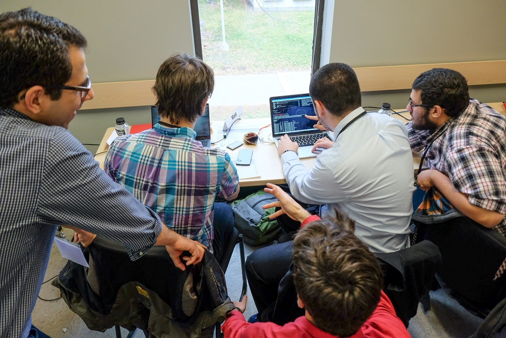 Four students working on computers, seen from behind.