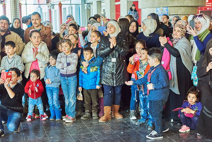 Un vaste groupe de réfugiés syriens, comprenant de nombreux enfants, pose devant la caméra.