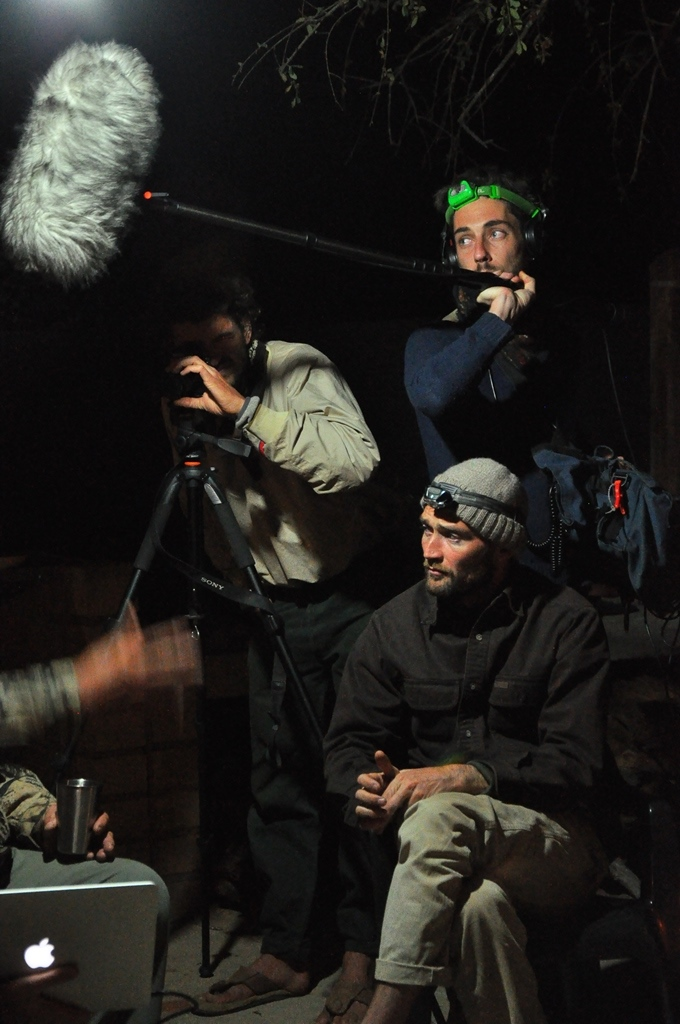 one sitting is wearing a knitted cap, one in the rear is holding a boom microphone and one is operating a camera on a tripod.