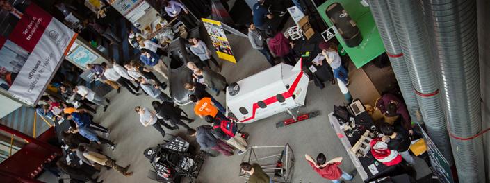 Vue en surplomb d'une vingtaine d'étudiants qui regardent un véhicule fermé muni de hublots ainsi que deux voitures dans un hall d'entrée.