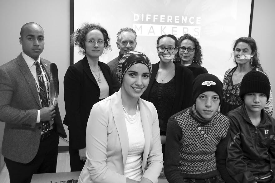 Un groupe composé d'hommes, de femmes et de jeunes pose pour la photo, avec pour toile de fond un écran illuminé avec les mots « Difference Makers » (Faites une différence).