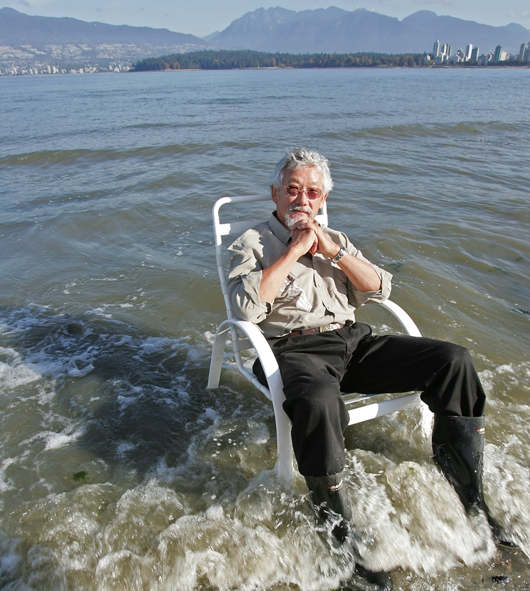 David Suzuki assis sur une chaise de jardin, posée directment dans l'eau d'une plage.