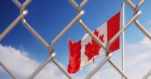 Drapeau canadien vu derrière une clôture câblée.