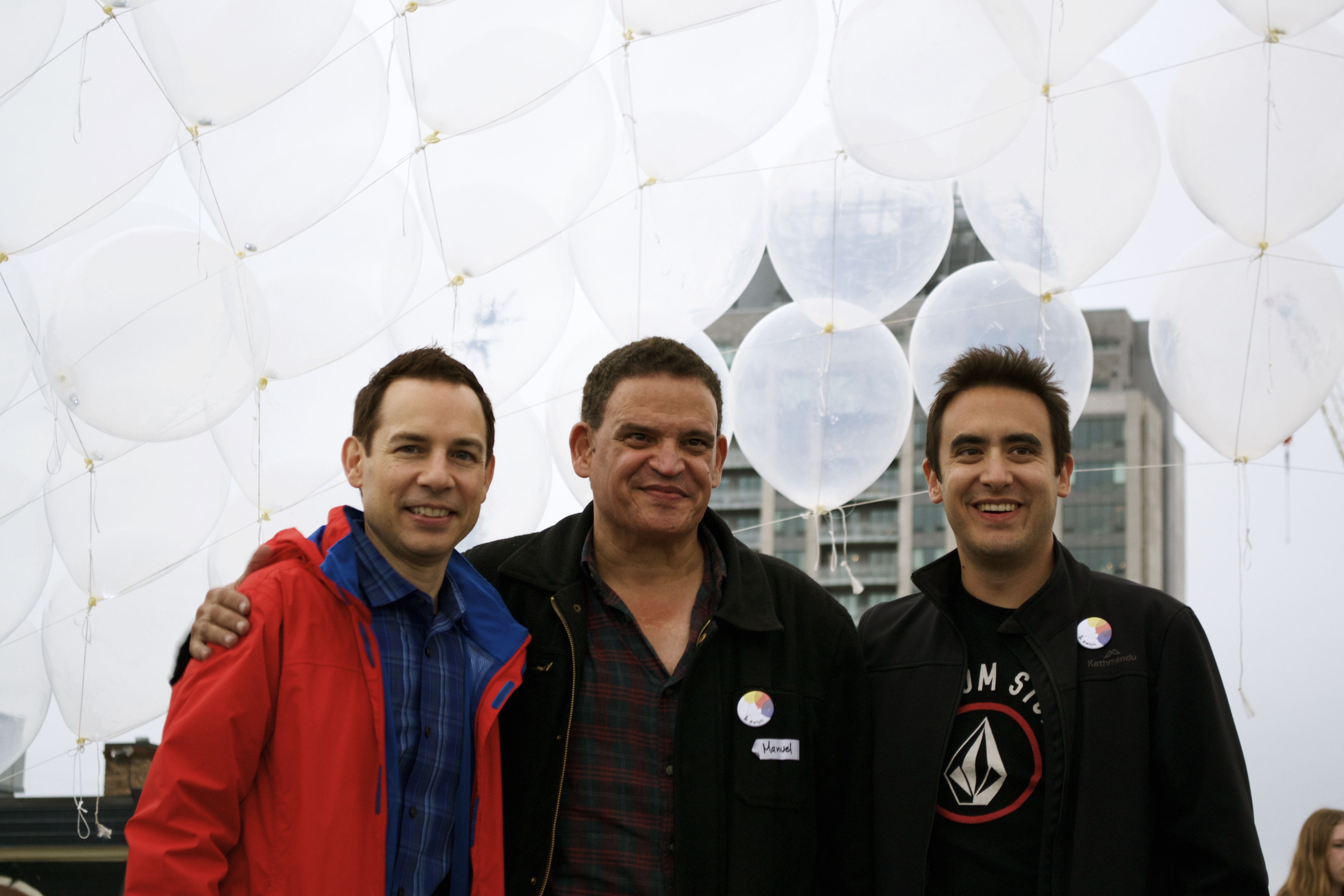 Three men smile for the camera with balloons floating overhead