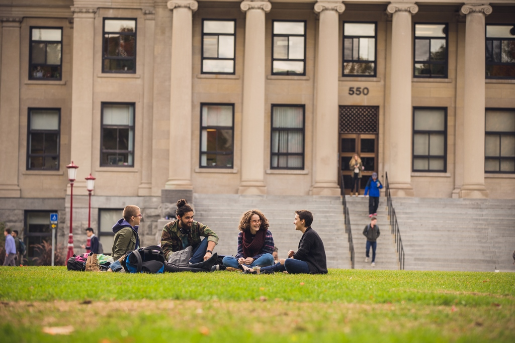 Four students sit on grass with Tabaret Hall columns and stairs in the background.